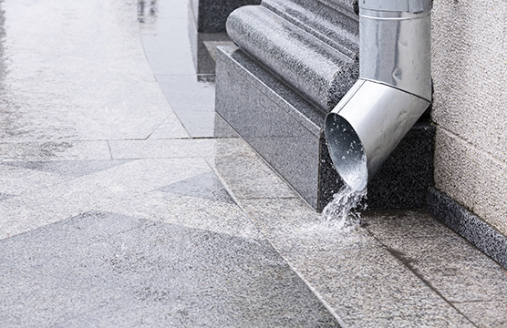 Rain water run out of a downspout during a thunderstorm
